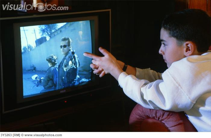 Watching television. (Young boy watching violence on television.)